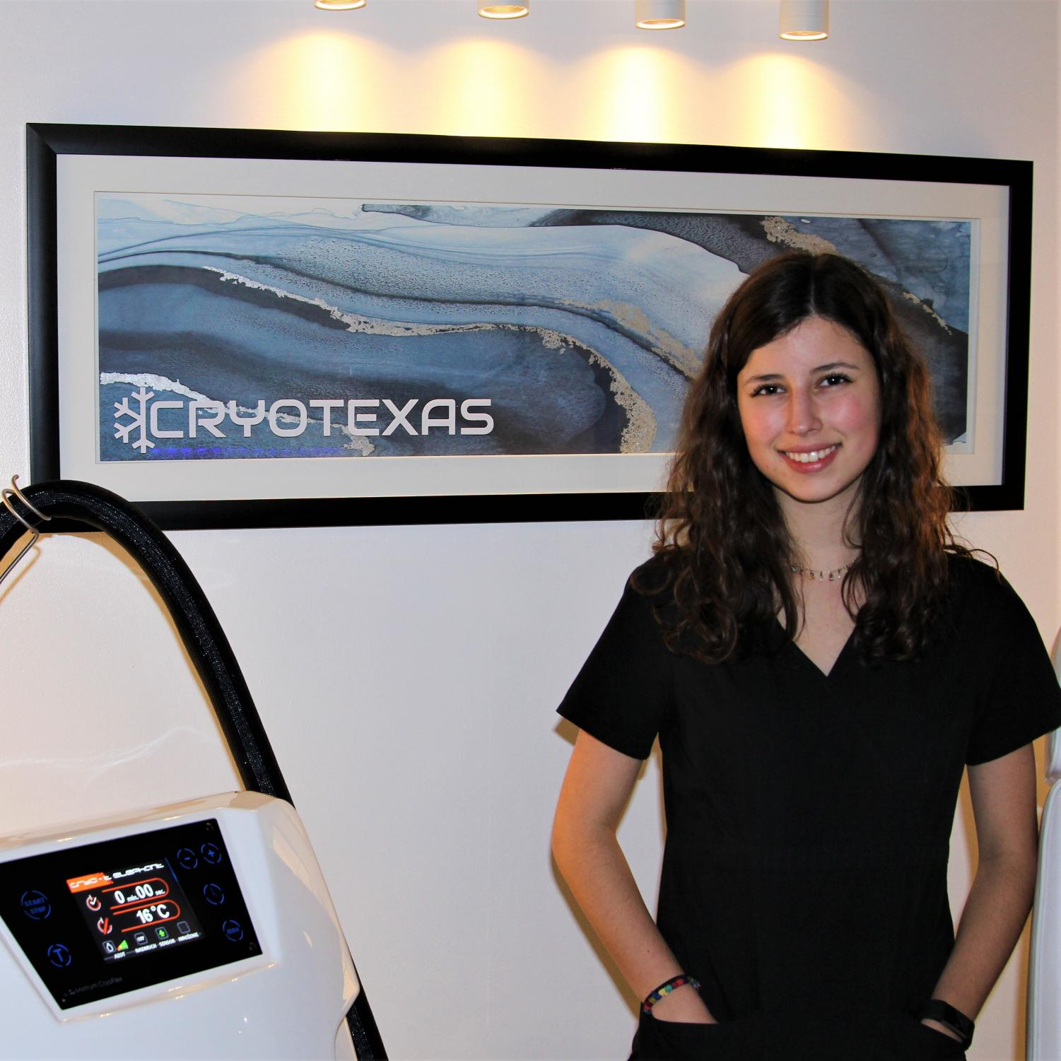 An employee at CryoTexas standing in front of one of the business's signs.